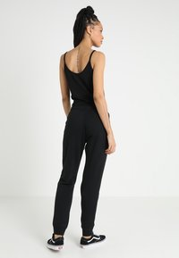 Nike Sportswear - RALLY  - Træningsbukser - black/white - 2