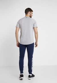 Under Armour - SPORTSTYLE GRAPHIC  - Träningsbyxor - academy/white - 2