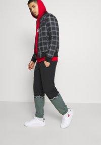 adidas Originals - SLICE TREFOIL ADICOLOR PRIMEGREEN ORIGINALS SLIM TRACK - Tracksuit bottoms - black/blue oxide - 3