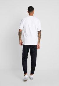 Nike Sportswear - TEARAWAY  - Tracksuit bottoms - black/white - 2