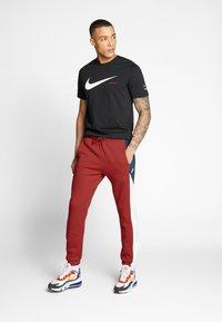 Nike Sportswear - Spodnie treningowe - university red/white - 1