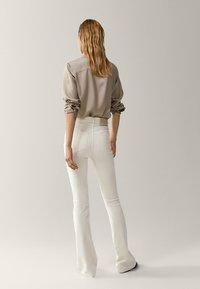 Massimo Dutti - SCHLAG AUS HOHEM  - Flared Jeans - beige - 2