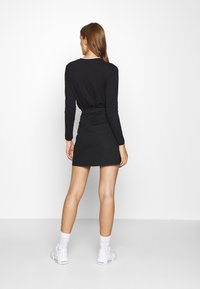 Calvin Klein Jeans - BUCKLE LOGO STRAP - Mini skirt - black