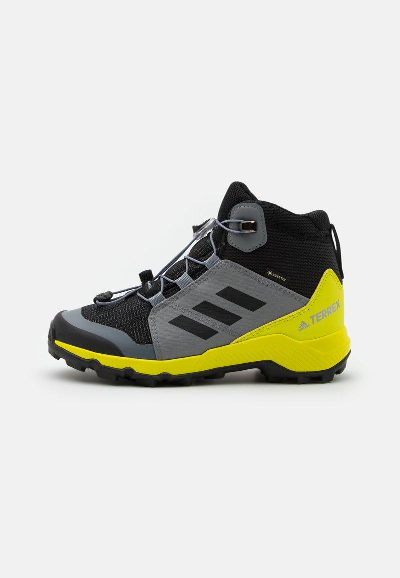 adidas Performance - TERREX MID GTX UNISEX - Hiking shoes - core black/grey three/acid yellow
