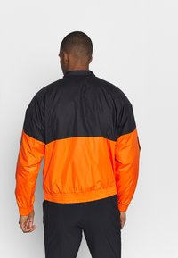 adidas Performance - Outdoor jacket - black/orange