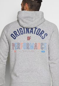 Under Armour - RIVAL ORIGINATORS HOODIE - Jersey con capucha - steel light heather/beta