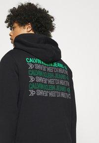 Calvin Klein Jeans - REPEAT TEXT GRAPHIC HOODIE UNISEX - Hoodie - black - 3