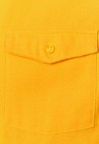 Nike SB - SOLID UNISEX - Camisa - university gold - 2