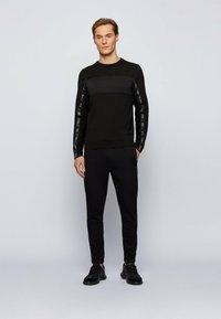 BOSS ATHLEISURE - Pantalon de survêtement - black - 1