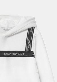 Calvin Klein Jeans - LOGO TAPE HOODIE UNISEX - Mikina skapucí - white - 2