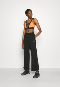 Puma - EMBROIDERED WIDE PANTS - Tracksuit bottoms - black - 1