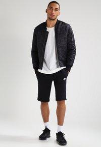 Nike Sportswear - CLUB - Tracksuit bottoms - schwarz/weiß - 1