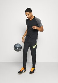 Nike Performance - DRY STRIKE PANT - Tracksuit bottoms - black/smoke grey/black/volt - 1