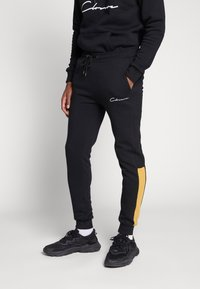 CLOSURE London - CONTRAST SCRIPT JOGGER - Tracksuit bottoms - black/mustard - 0