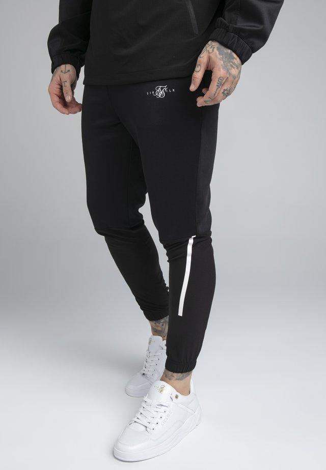 TRANQUIL TRAINING PANT - Teplákové kalhoty - black/grey