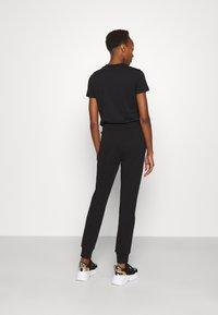 Versace Jeans Couture - PANTS - Tracksuit bottoms - black - 2