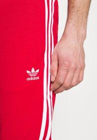 adidas Originals - UNISEX - Tracksuit bottoms - scarle/white - 4