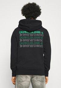 Calvin Klein Jeans - REPEAT TEXT GRAPHIC HOODIE UNISEX - Hoodie - black - 2