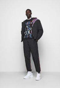 Versace Jeans Couture - CRINKLE  - Tracksuit bottoms - nero - 1