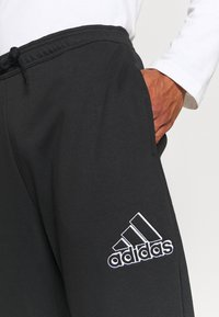 adidas Performance - ESSENTIALS RELAXED - Tracksuit bottoms - black - 3