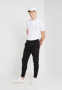 Polo Ralph Lauren - Pantalon de survêtement - black/gold - 1