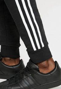adidas Originals - STRIPES PANT UNISEX - Pantalon de survêtement - black - 6