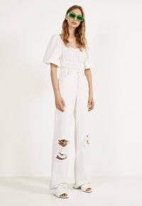 Bershka - MIT SCHLAGHOSE UND RISSEN - Jeans Relaxed Fit - white - 1