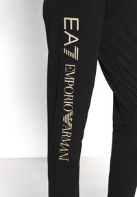 EA7 Emporio Armani - Pantalones deportivos - black/light gold - 3