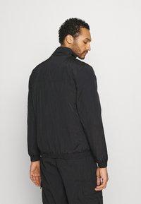Karl Kani - SIGNATURE TRACKJACKET UNISEX - Summer jacket - black - 2