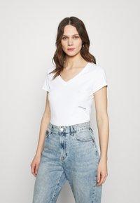 Calvin Klein Jeans - MICRO BRANDING OFF PLACED VNECK - Basic T-shirt - bright white - 0