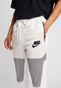 Nike Sportswear - PANT BODYMAP - Tracksuit bottoms - light bone/summit white/black - 5