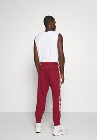 Nike Sportswear - REPEAT  - Tracksuit bottoms - team red - 2