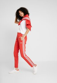 adidas Originals - SUPERSTAR SUPER GIRL ADICOLOR TRACK PANTS - Spodnie treningowe - lush red/white - 1