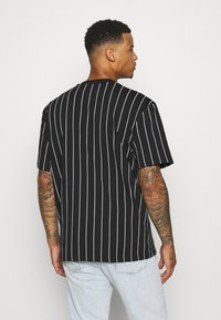 Karl Kani - SMALL SIGNATURE PINSTRIPE TEE UNISEX - T-shirt med print - black/white - 2