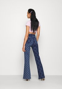 Jaded London - FLOWER DISCHARGE PRINT WITH HEART BUTTON - Bootcut jeans - blue