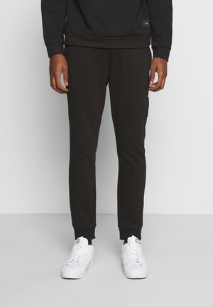 COMBAT - Tracksuit bottoms - black