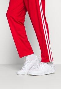 adidas Originals - Tracksuit bottoms - scarle/white - 4