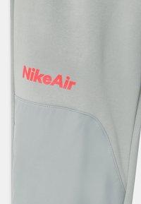 Nike Sportswear - AIR - Tracksuit bottoms - light smoke grey/bright crimson - 2