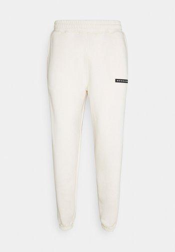 AFTERMATH RUBBER BADGE UNISEX - Pantalon de survêtement - off white