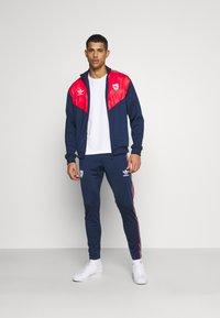 adidas Originals - Tracksuit bottoms - collegiate navy - 1