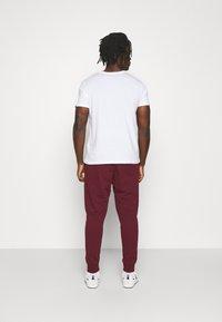 Nike Sportswear - CLUB - Tracksuit bottoms - dark beetroot/white - 2