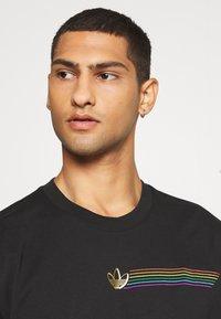 adidas Originals - PRIDE SHORT SLEEVE GRAPHIC TEE - T-shirts med print - black - 3
