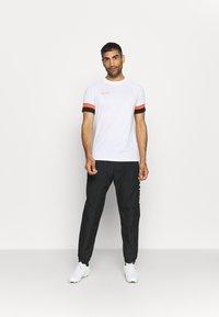 Nike Performance - T-shirt z nadrukiem - white/black/bright crimson - 1