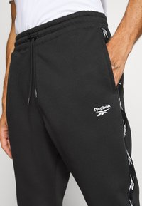 Reebok - TAPE JOGGER - Tracksuit bottoms - black - 4