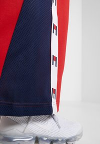 Tommy Sport - FLAG TAPE PANT FLARE - Träningsbyxor - red - 6