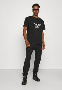 More Joy by Christopher Kane - MORE JOY EMBROIDERED CLASSSIC JOGGERS UNISEX - Tracksuit bottoms - black/white - 1