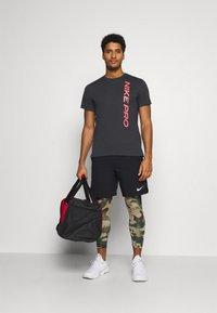 Nike Performance - BURNOUT - Print T-shirt - black/bright crimson - 1