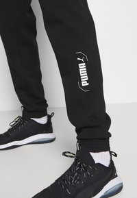 Puma - NU TILITY PANTS - Tracksuit bottoms - black - 3