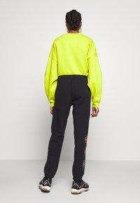 Nike Sportswear - PEACE PACK PANT - Joggebukse - black/green spark - 2