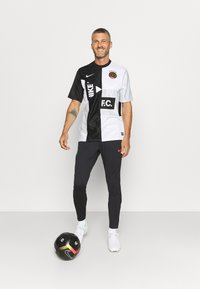 Nike Performance - FC PANT - Spodnie treningowe - black/iridescent/habanero red - 1